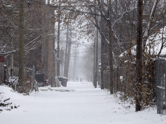 Two people walk through an alley while snow continues to fall on Sunday, Dec. 11, 2016 in the Woodbridge neighborhood in Detroit.