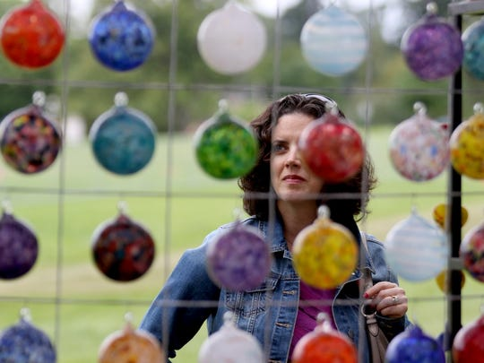 A woman looks at glass art available during the 67th annual Salem Art Fair and Festival at Bush's Pasture Park. Applications for artists for this year are due Feb. 10.