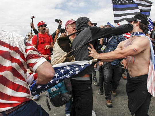 Supporters of President Donald Trump scuffle with counter-protesters during a rally on Saturday, March 25, 2017, in Huntington Beach, Calif.