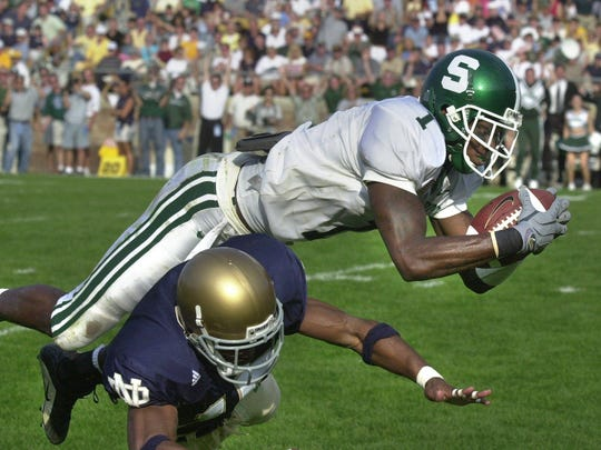 MSU wide receiver Charles Rogers leaps into the endzone over Notre Dame defender Clifford Jefferson to score the winning touchdown on a 47-yard pass play from quarterback Ryan Van Dyke in South Bend on Sept. 22, 2001.