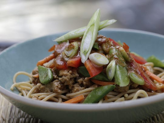 An Asian Chicken Noodle Bowl consists of whole-wheat noodles topped with ground chicken and served with vegetables and a peanut sauce.