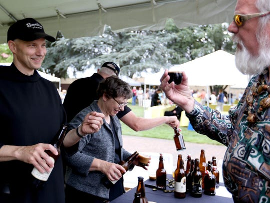 Father Martin Grassel, left, gives a beer sample to Dale Small, of Silverton, at the Mount Angel Abbey Saint Benedict Festival in 2015.