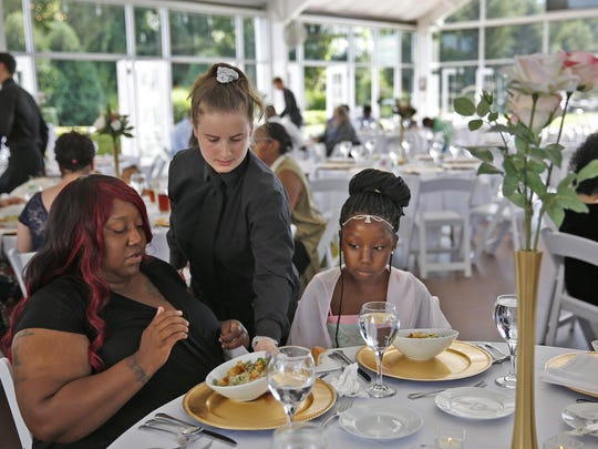 Katelin Decraene, center, gives Trishell Crawford and her daughter Jacqueline Crawford, from Dayspring, salads at a reception at the Ritz Charles on Saturday. Sarah Cummins called off her wedding which was supposed to be this day. Cummins decided to bring purpose to the couple's pain by inviting area homeless to enjoy the reception.