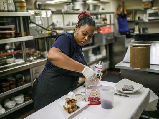 Pastry Chef Crystal Smith plates one of her desserts,