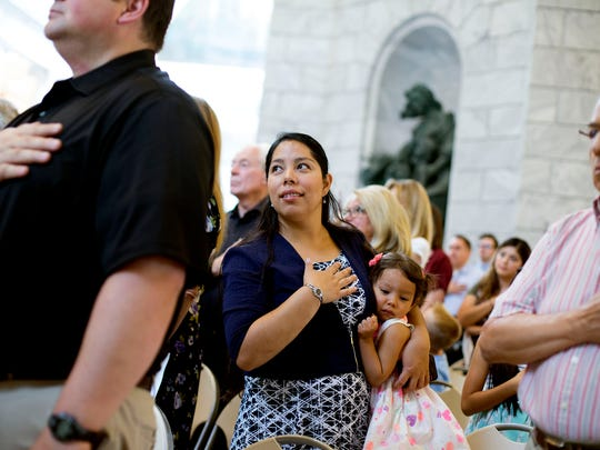 Martha Madariaga Borden and her daughter, Ariana, stand during the national anthem during a naturalization ceremony for approximately 125 people from more than 40 countries at the state Capitol in Salt Lake City on Wednesday, July 19, 2017. Borden's husband was one of the those who became citizens.