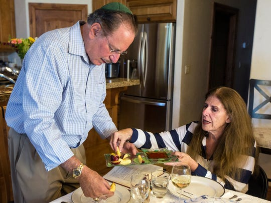 """Larry and Laura Green dip apples in honey in hope of a """"sweet"""" new year during a Rosh Hashana dinner at their house in Sandy on Sunday, Sept. 9, 2018."""