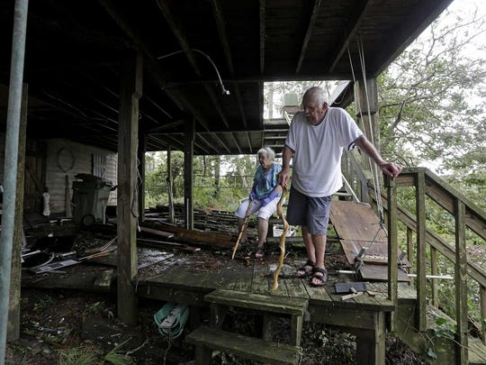 Elton and Claudia Matheson, who rode out the storm, looks at the damage from the high water under his home after Hurricane Florence hit Emerald Isle N.C.,Sunday, Sept. 16, 2018.
