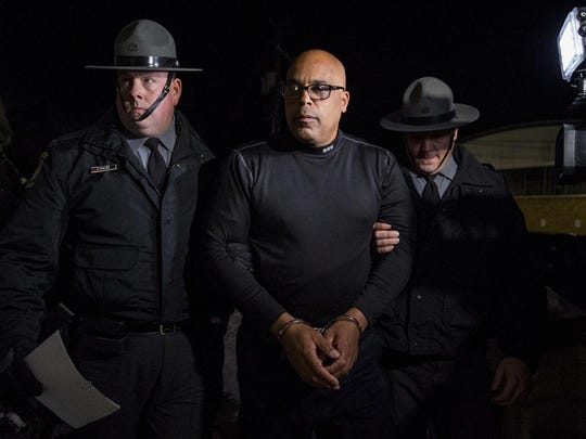 Pennsylvania State Troopers escort Wilkes-Barre, Pa. city police officer Robert Collins, 53, center, of Mountain Top, Pa., into magistrate David A. Barilla's office in Forty Fort, Pa., Tuesday, Jan. 19, 2019, after Collins was arrested on charges that he sexually assaulted several women while on duty and threatened the women to keep quiet about it. Collins says he plans to fight the charges, telling a judge he passed a lie detector test. (Christopher Dolan/The Citizens' Voice via AP)