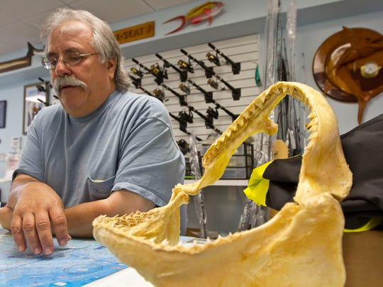 Dave Arbeitman, seen here in 2014 at his business The Reel Seat in Brielle with the jaws of a former state record dusky shark, has passed away, the shop announced Sunday.