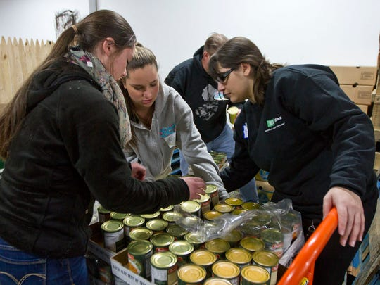 Volunteers Carlie Caruso, 17, Katelyn Caruso, 14, and Brittney Trevisan load a pallet with canned vegatables. The People's Pantry Relief Center distributes turkey dinners with all the fiixings to more than 500 people. Toms River, NJ Friday, November 22, 2014 Doug Hood/Staff Photographer