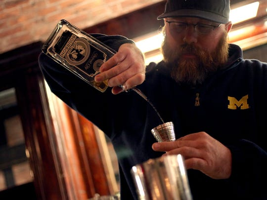 Chuck Gellasch, 38, tasting room manager at Detroit City Distillery in Detroit, pours some of the distillery's bourbon for a drink.