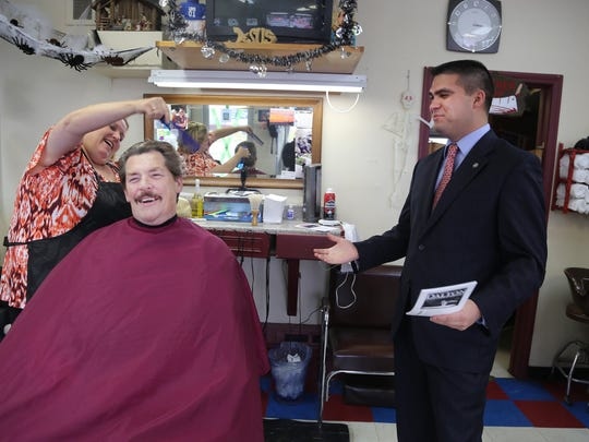 Tom Reimer, 71, of Livonia gets his hair cut by Michelle Cid, 47, of Livonia as John Dalton, 24, of Livonia, the Republican candidate for Wayne County executive, campaigns at a Livonia barber shop  on Thursday, Oct. 30, 2014. Reimer tells the candidate he already voted and in fact he and his wife already voted for him.