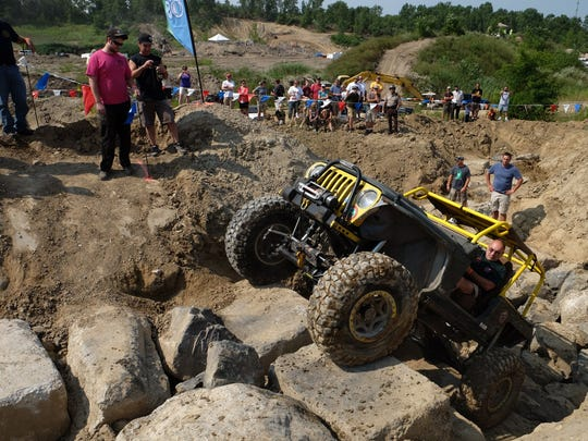 """Jiri Muller, 57, of Rochester Hills drives his modified Jeep TJ with competition-style """"sticky"""" tires up a hill of boulders in August in a test by off-road vehicle clubs to see whether an old gravel mine in north Oakland County could be turned into a regional ORV playground — to be Michigan's first that is near metro Detroit. ORV fans can make more test runs this weekend at an event that's open to spectators at $5 per person."""