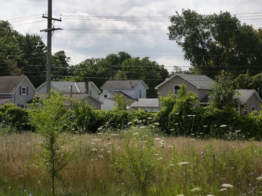 A view of homes July 30, 2014, near the site where the Velsicol Chemical produced various chemical compounds and products on its 54-acre main plant site in St. Louis, Mich., in 1936-78.