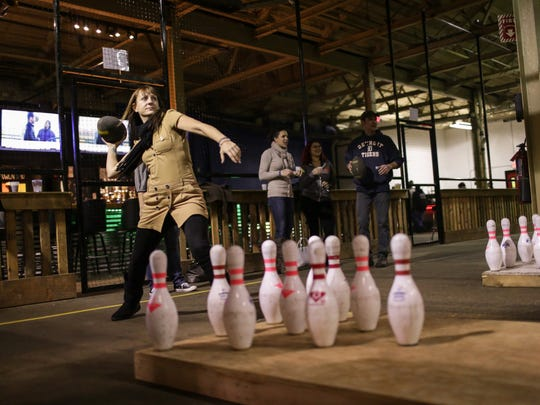 Amy Memminger of Hamtramck winds up to toss a football at bowling pins at the other end of the lane at the Fowling Warehouse in Hamtramck. The new nightlife spot features the game where people use a football to knock down bowling pins.