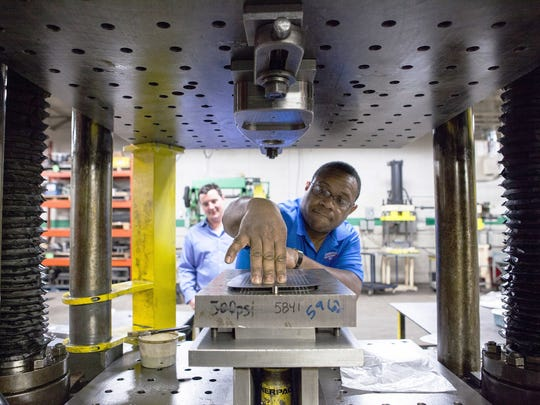 Fred Pinkston, supervisor at Sherwood Prototype, positions a metal piece in a stamping press. He has worked for the company for 24 years. Lance Paxton in background.