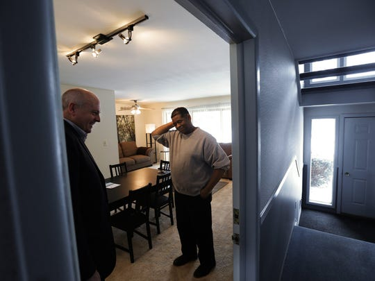 UBS banker Blake Pollock, 47, of Rochester says good-bye to James Robertson after visiting him with others in his new apartment on Tuesday March 3, 2015.