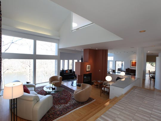 Long view of the living room with floor to ceiling windows with view to the peaceful Huron River