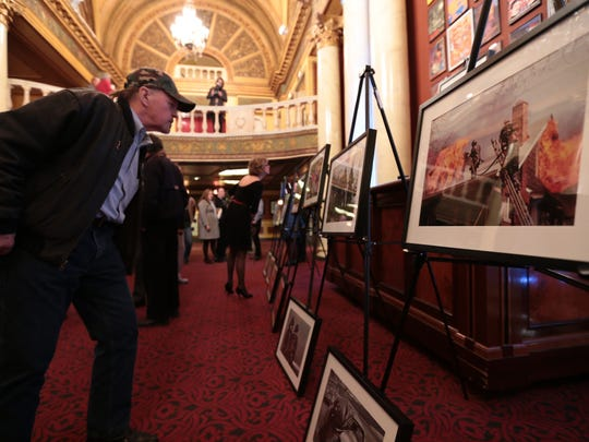"Terry Glosser of Clinton Township looks over photos from photographer Bill Eisner before the film ""Fire Photo -> 1"" during the opening night of the 2015 Freep Film Festival on Thursday at the Filmore Detroit in downtown Detroit."