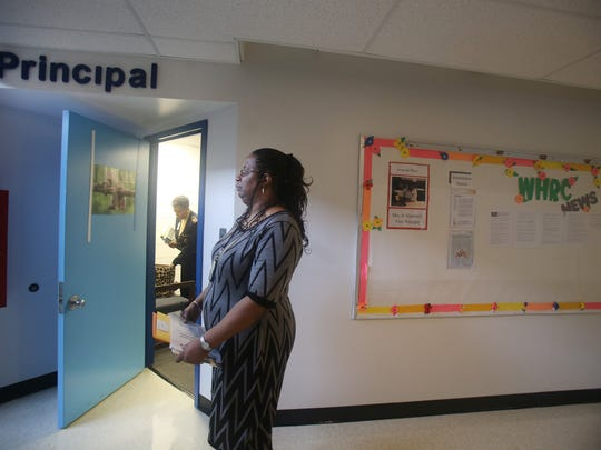 Michelle Peguese works for the Department of Human Services as a Success Coach for the Pathways to Potential program at WHRC Elementary School in Pontiac. She is waiting to meet with the school's principal Wendy Fitzpatrick.