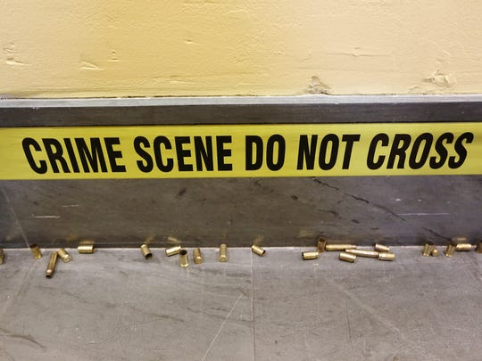 "Crime scene tape surrounds the exhibit room for the traveling art exhibit, ""Kin Killin' Kin,"" at Central Library. Spent gun shells litter the floor, as well."