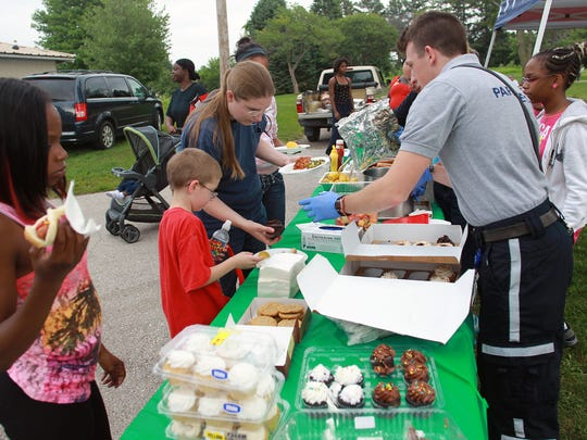 Laura Aamodt of Iowa City helps her children choose their dinner Tuesday during National Night Out at Wetherby Park .