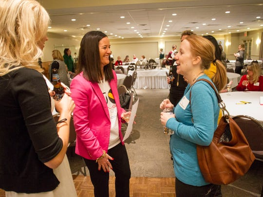 Vanessa McDonald chats with members of the Hawkeye Chapter of 100+ Women Who Care before their meeting at The University Club on Dec. 18.