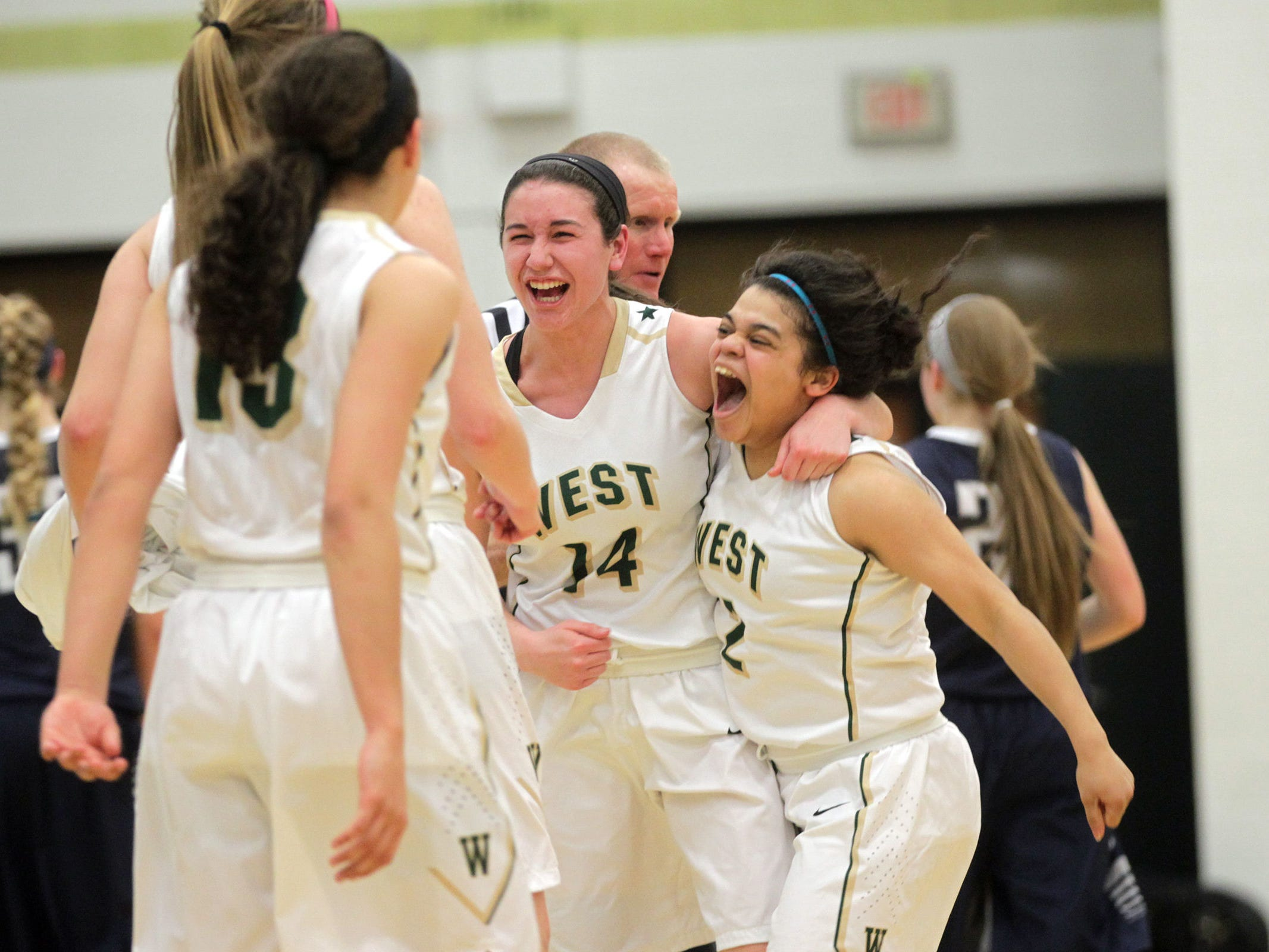 West High senior Dani Craig, center, celebrates with classmate Bella Lozano-Dobbs following the Women of Troy's Class 5A regional final against Pleasant Valley on Tuesday, Feb. 24, 2015. West High won, 45-27, to advance to the state tournament. David Scrivner / Iowa City Press-Citizen