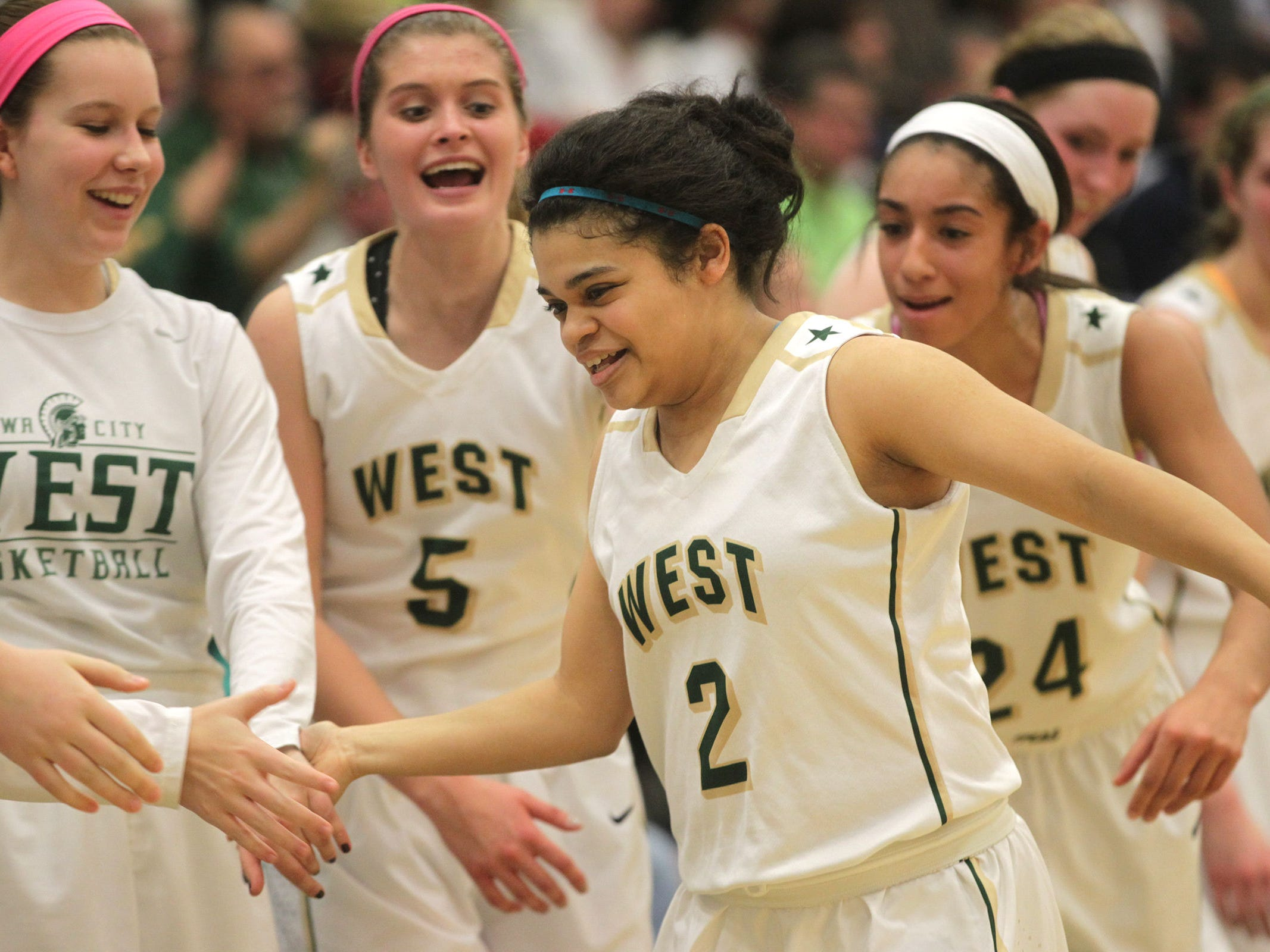 West High senior Bella Lozano-Dobbs gets high-fives as she heads to the bench in the final minute of the Women of Troy's Class 5A regional final against Pleasant Valley on Tuesday, Feb. 24, 2015. West High won, 45-27, to advance to the state tournament. David Scrivner / Iowa City Press-Citizen
