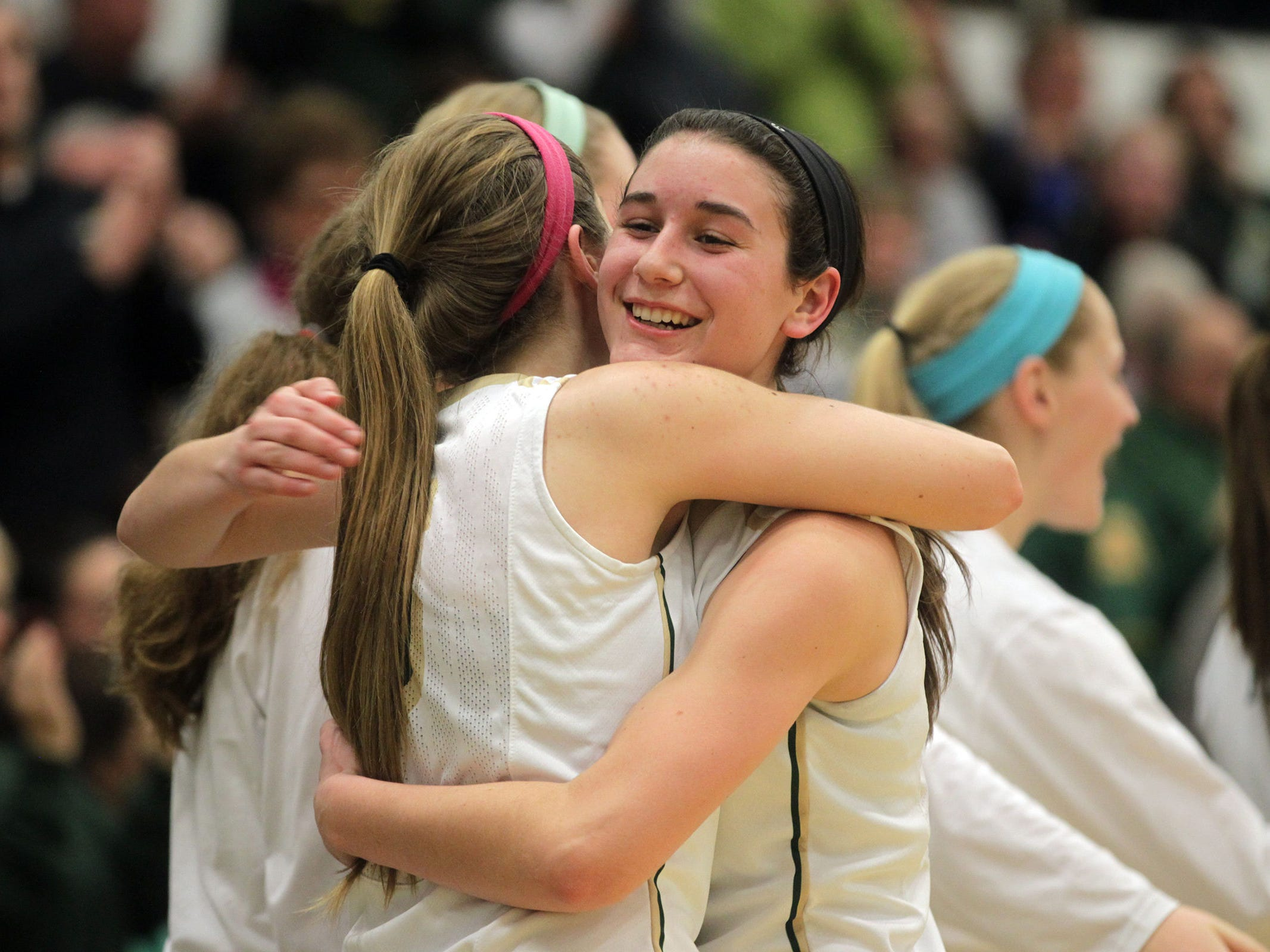 West High senior Dani Craig, right, hugs classmate Grace Tafolla in the final minute of the Women of Troy's Class 5A regional final against Pleasant Valley on Tuesday, Feb. 24, 2015. West High won, 45-27, to advance to the state tournament. David Scrivner / Iowa City Press-Citizen