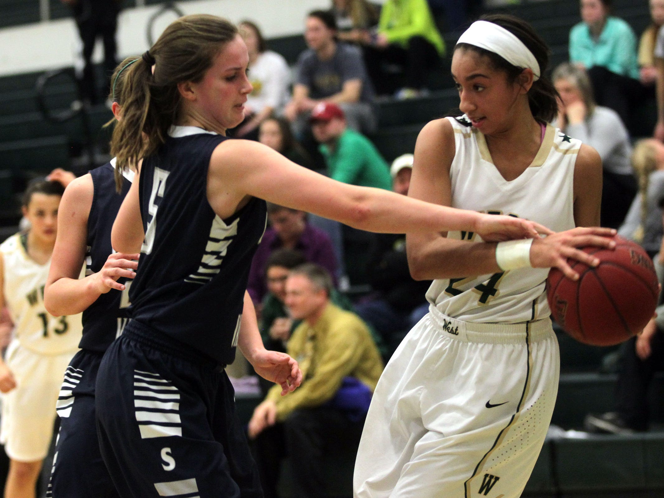 West High's Mikaela Morgan guards the ball from Pleasant Valley's Rory Donahue during their Class 5A regional final on Tuesday, Feb. 24, 2015. West High won, 45-27, to advance to the state tournament. David Scrivner / Iowa City Press-Citizen