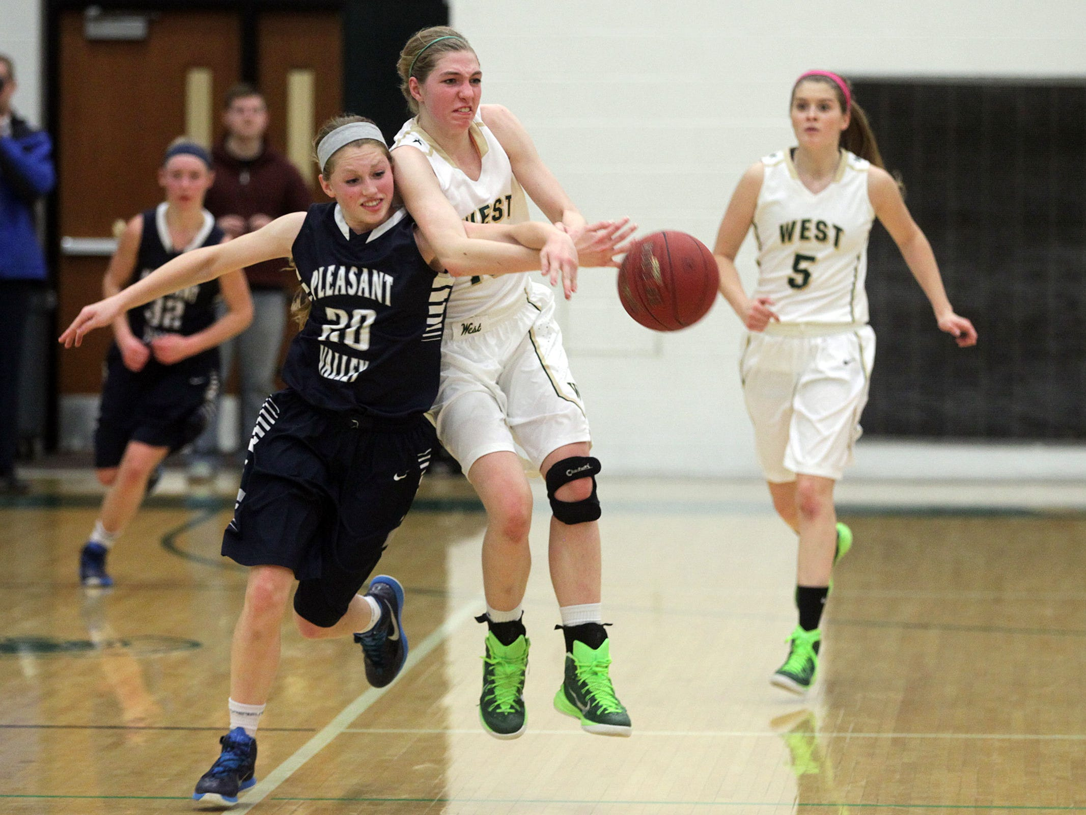 West High's Ali Tauchen steals the ball from Pleasant Valley's Kira Arthofer during their Class 5A regional final on Tuesday, Feb. 24, 2015. West High won, 45-27, to advance to the state tournament. David Scrivner / Iowa City Press-Citizen