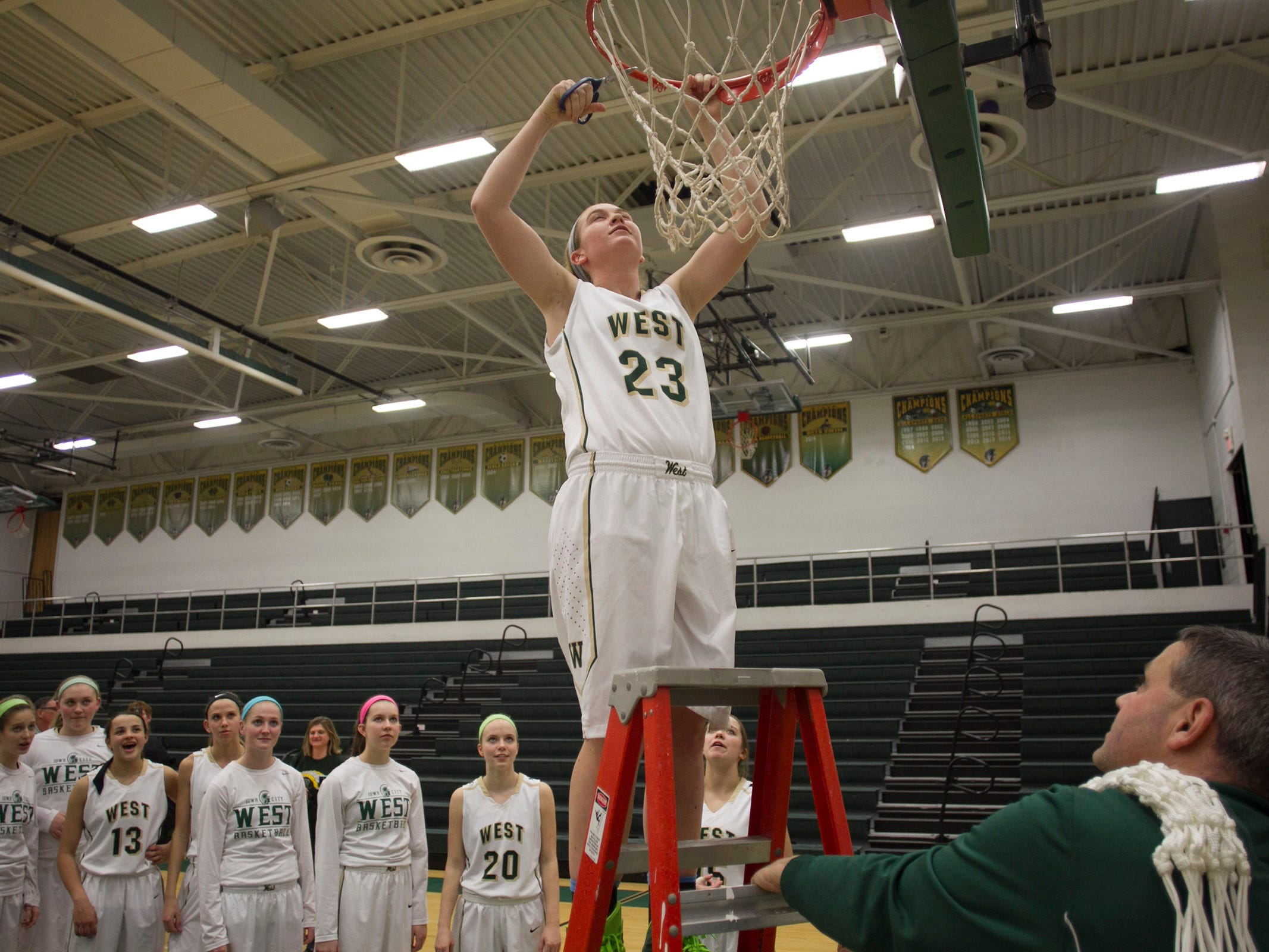 West High's Jessie Harder helps cut down the net following the Women of Troy's Class 5A regional final against Pleasant Valley on Tuesday, Feb. 24, 2015. West High won, 45-27, to advance to the state tournament. David Scrivner / Iowa City Press-Citizen