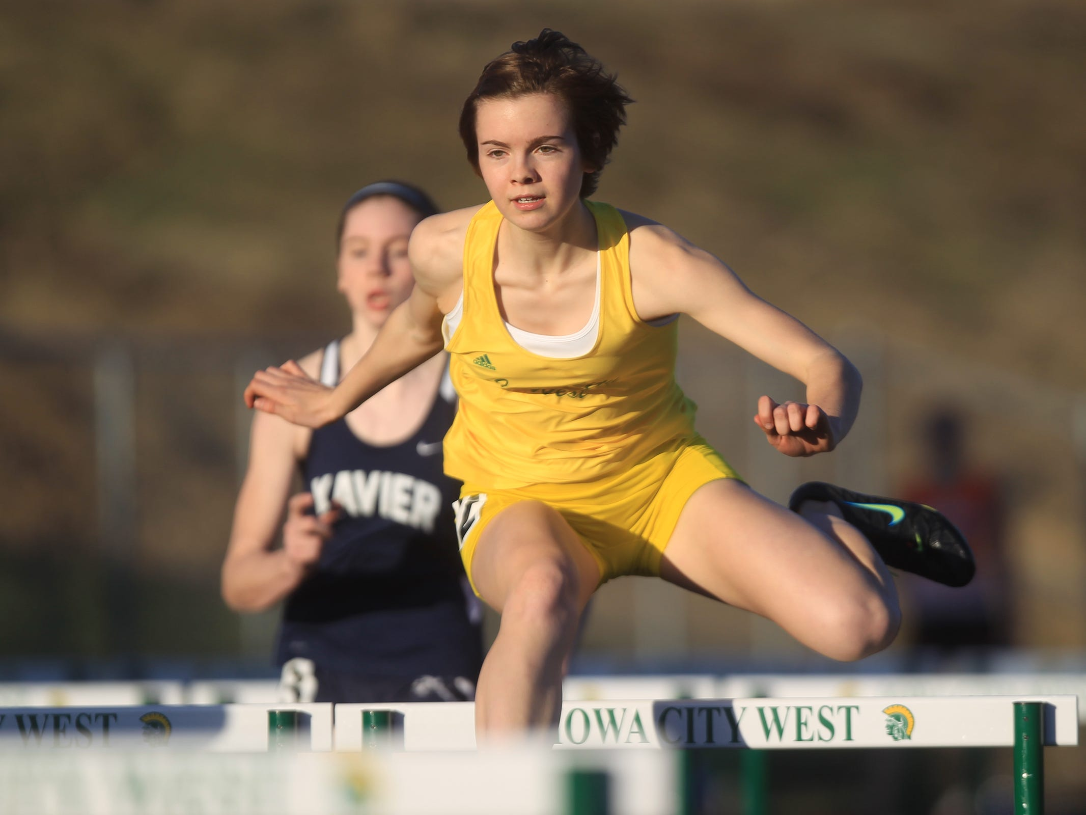West High's Grace Young competes in the 100 meter hurdles at the Women of Troy Relays at West High on Tuesday, March 31, 2015. David Scrivner / Iowa City Press-Citizen