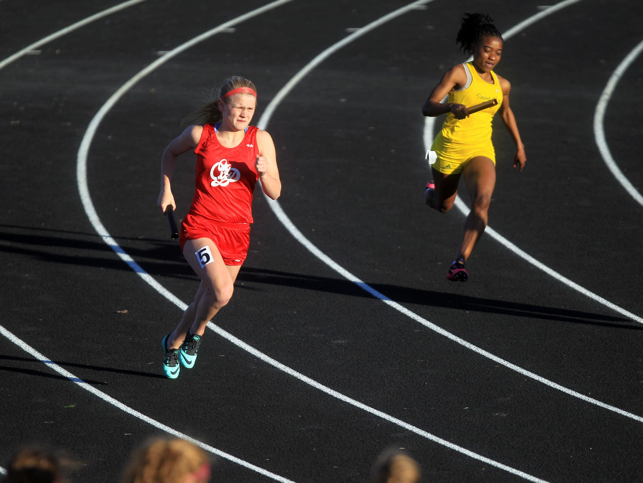 City High's Sydney DePrenger and West High's Katherine Mukumbilwa compete in the 4x200 meter relay at the Women of Troy Relays at West High on Tuesday, March 31, 2015. David Scrivner / Iowa City Press-Citizen