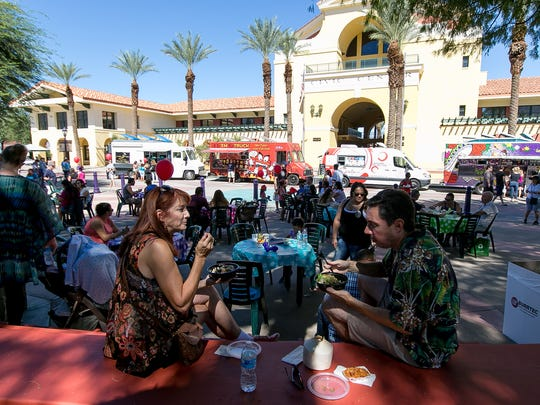 Lolita Falk (left) and Tony Garcia, both of Palm Springs, enjoy lunch under a shade during Cathedral City Farmers Market and National Fire Prevention Week Celebration held at the Cathedral City Civic Center on Sunday morning.