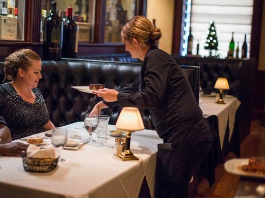 Tournedos' server Lyndsey Bridges of Irondequoit serves Eugenia Avery of Rochester at the restaurant, 26 Broadway.