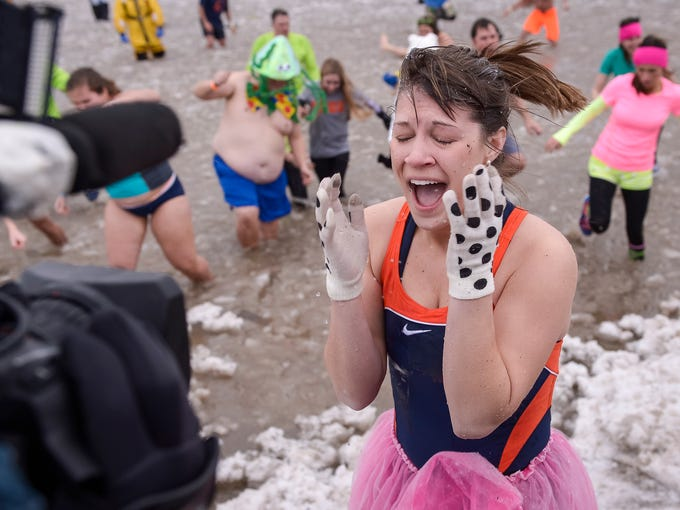 A Polar Plunge participant screams in front of a news