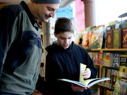 Gabriel Humphreys, 11, of Salem and his dad, Adam Humphreys, look through books together at the Book Bin in downtown Salem.