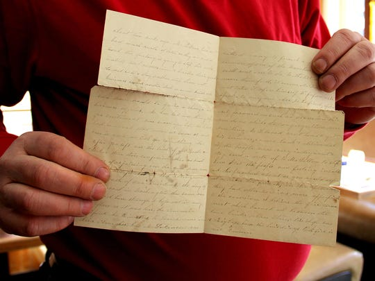 Goebel holds the tattered, yellowed and fragile piece of correspondence written nearly 150 years ago about events in Salem.