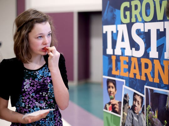 Kaitlyn Green, a seventh-grader, tries a Pacific rose apple during the lunch period at Leslie Middle School in Salem on Thursday, Feb. 19, 2015. A cooperation with FoodCorps, the Salem-Keizer Education Foundation, and LifeSource Natural Foods gives students to opportunity to try potentially new fruits and vegetables during their lunch period.