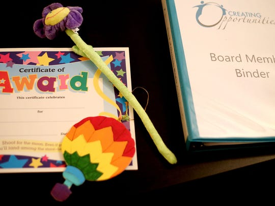 Awards for children and their families sit with meeting materials during a Creating Opportunities board members meeting Friday, Feb. 27, in Dallas.