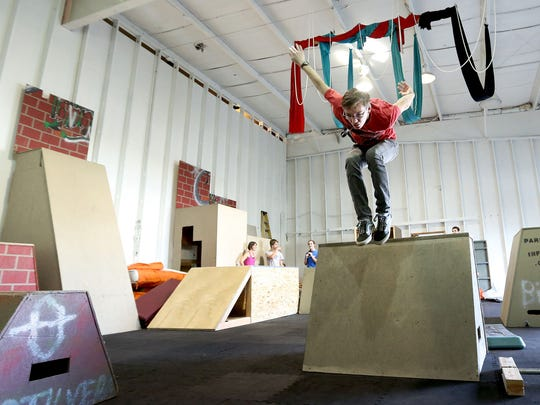 Keenen Farrell, 18, of Dallas leaps off an obstacle during a parkour class at Parkour Infinity.
