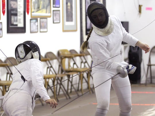 Olivia Merten (facing), 16, of Corvallis, bouts with Justin Gonzalez, 12, of Salem, at the Salem Fencing Club on Wednesday.