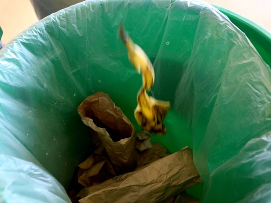 A banana peel is tossed in the food waste bin on the first day of a food waste composting project at South Salem High School on Monday, April 6, 2015.