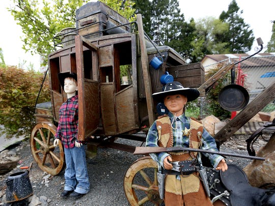 Rick Byrd, 60, of Salem, has placed a stagecoach, complete with a lantern and other period-pieces, outside his wife's business, the Oh My Dog Pet Salon in northeast Salem. Photographed on Monday, April 13, 2015.