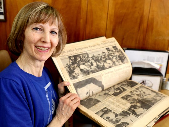 Joyce Epp, executive director of Salem Youth Symphony Association, looks at scrapbook clips from her organization's history during the Statesman Journal's Holding Court.