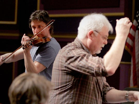 Guest soloist Peter Frajola (left) plays as Larry Garrett conducts the Salem Youth Symphony at North Salem High School in a rehearsal for the ensemble's 60th anniversary concert which will be at 3 p.m. May 3 at Willamette University's Smith Auditorium.