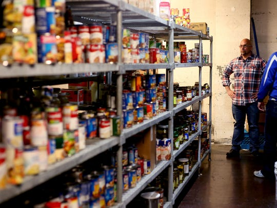 Food services manager Michael Kerrigone, left, works with Joshua Schrantz on Friday, April 24, in the canned food storage area at the Union Gospel Mission in Salem.
