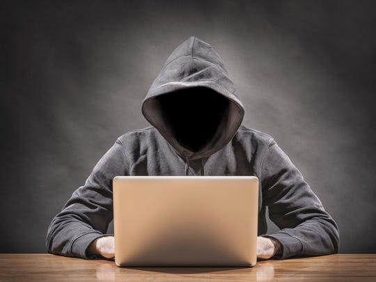 Someone in a hooded sweatshirt with their face obscured, illustrating cybercrime.